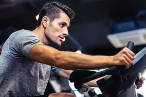 Side view portrait of a man workout on a fitness machine at gym