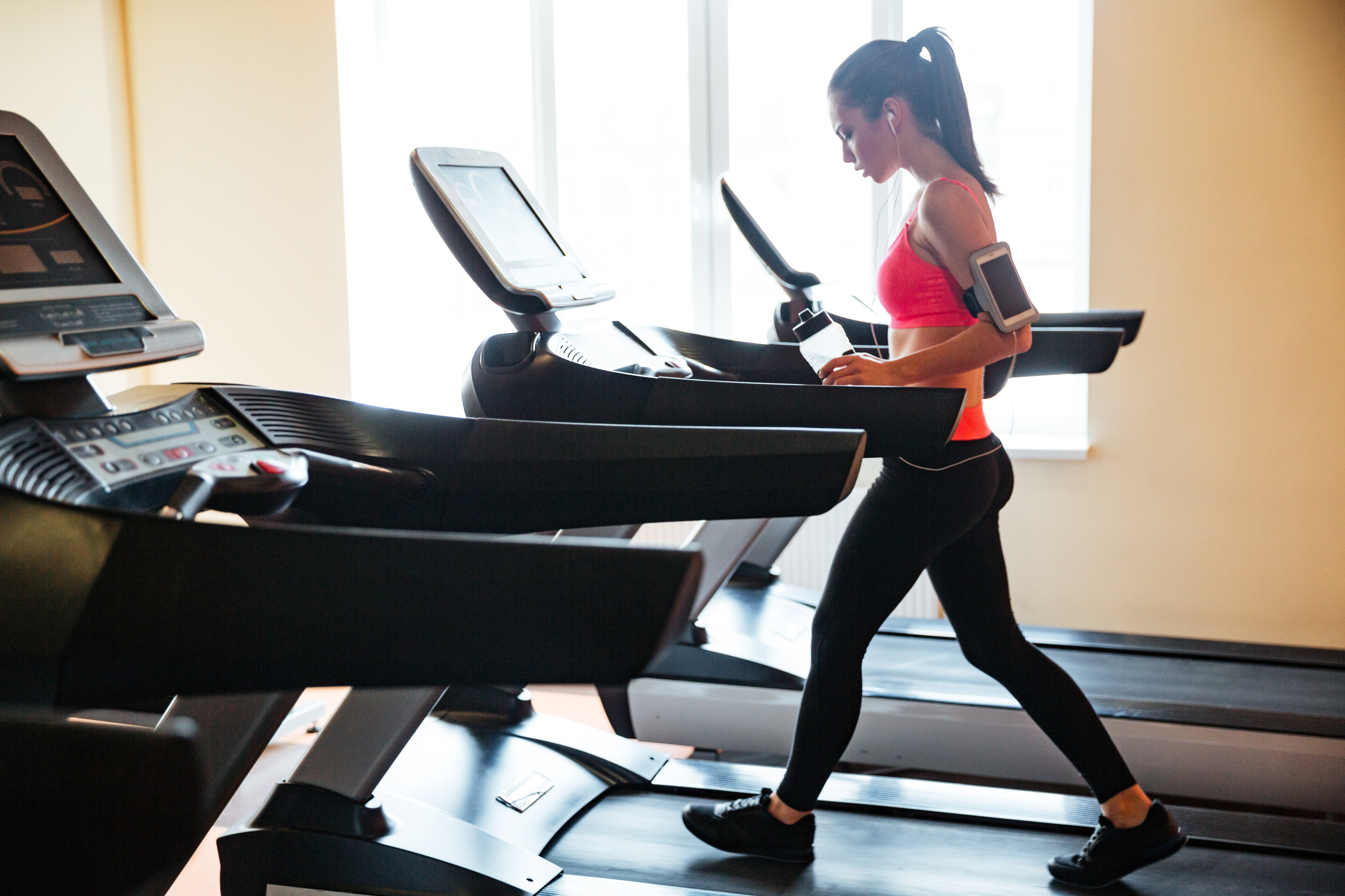 beautiful-young-sportswoman-with-earphones-and-blank-screen-smartphone-using-treadmill-and-drinking-water-in-gym_BKaJICSo.jpg