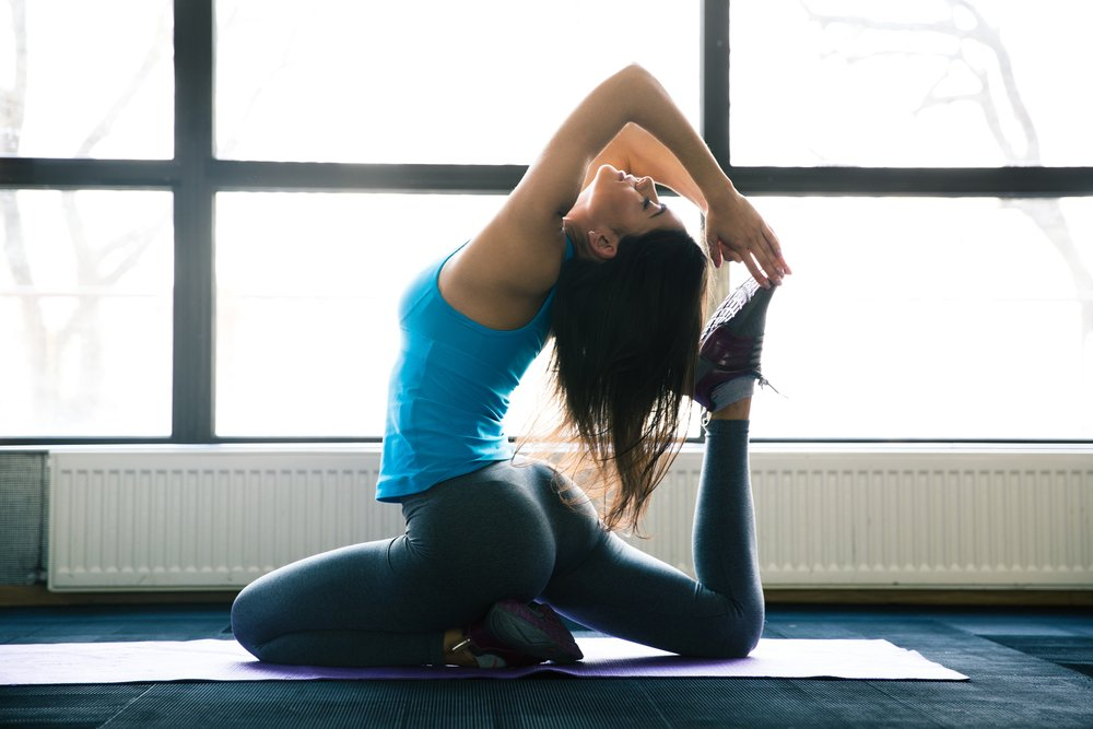 Young woman doing yoga exercises on yoga mat at gym
